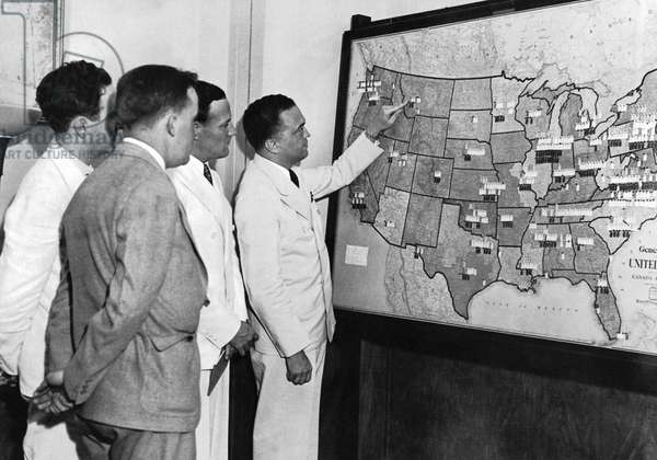 JOHN EDGAR HOOVER (1895-1972). American lawyer and public official. Photographed in 1935 pointing to a map of the United States used to represent the course of federal crime investigations.
