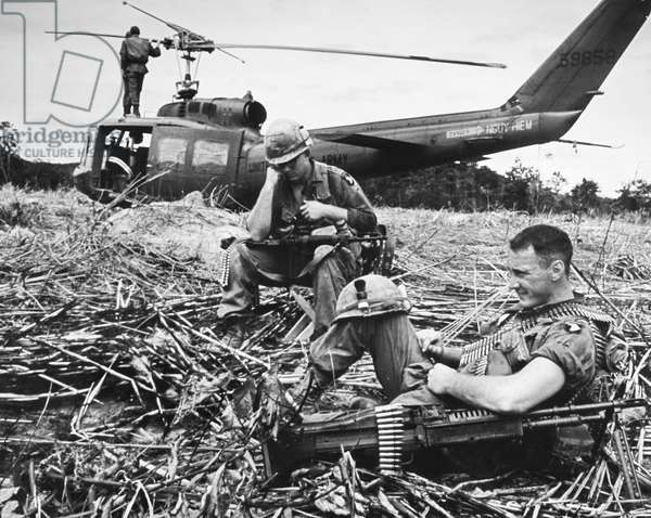 VIETNAM WAR: HELICOPTER The crew of an American helicopter take a rest, weapons at the ready.