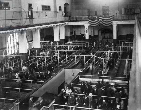 ELLIS ISLAND: IMMIGRANTS. Immigrants waiting to be processed in the reception hall at Ellis Island, c.1900.