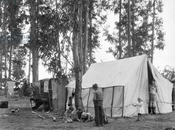 A group of children playing in front of their tent in a migrant worker camp, rural California, 1935 (b/w photo)