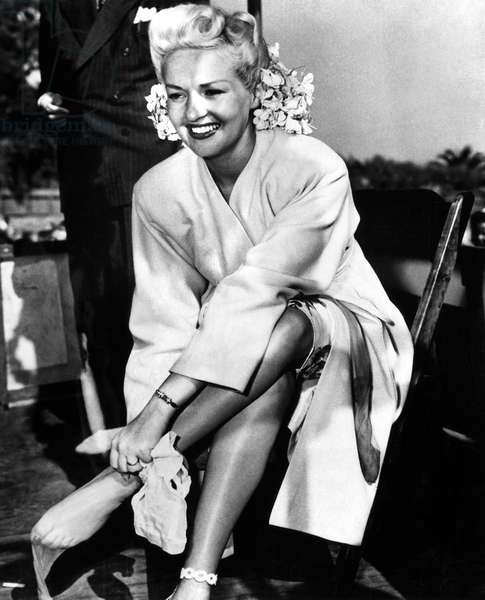 BETTY GRABLE (1916-1973) American actress. Auctioning her nylon stockings for ,000 at a war bond rally in California. Photograph, c.1943.