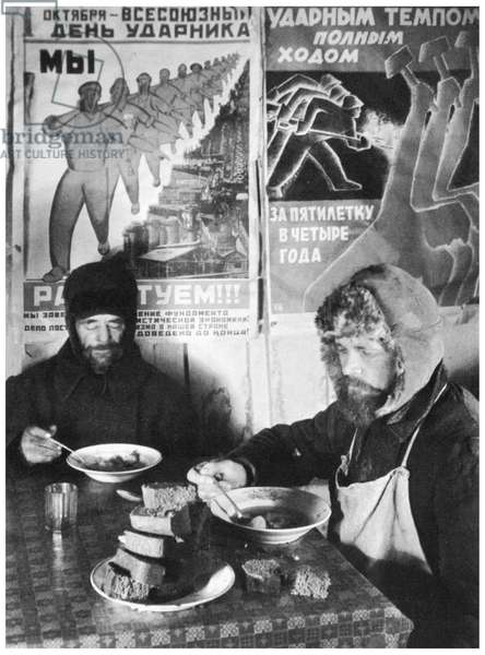 Russian bricklayers dining in a communal kitchen, under Soviet posters urging increased worker productivity during the first five-year plan, 1932.