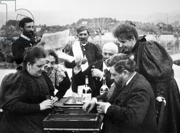 LUMIERE BROTHERS, 1896 Auguste, standing left, and Louis Lumiere, standing center, the French motion picture pioneers, with friends playing backgammon at La Ciotat on the French Riviera, 1896.