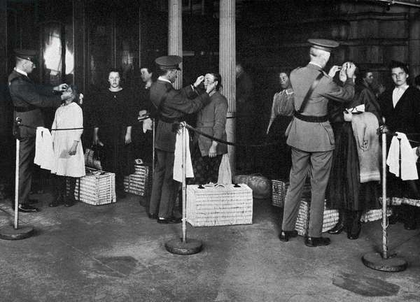 ELLIS ISLAND: EXAMINATION Immigrants being examined for eye diseases at Ellis Island, early 20th century.