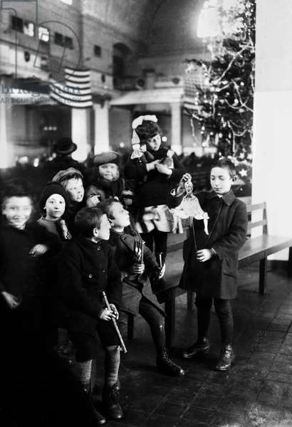 ELLIS ISLAND: CHRISTMAS Group of immigrant children celebrating Christmas in the registry room at Ellis Island, New York City. Photograph, 1920.