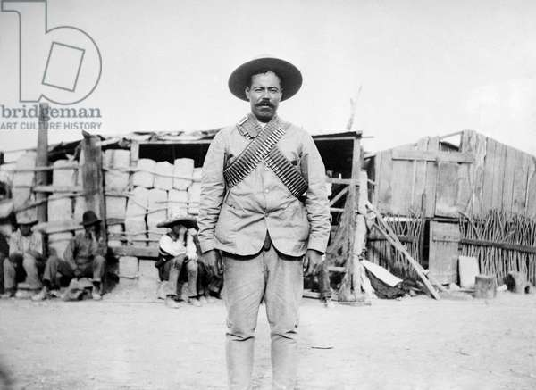 FRANCISCO 'PANCHO' VILLA (1878-1923). Mexican revolutionary leader. Photographed wearing bandoliers in front of an insurgent camp, c.1914.