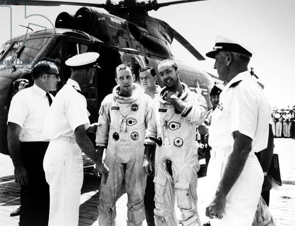 GEMINI IV: ASTRONAUTS, 1965 Gemini IV astronauts Edward White (center left) and James McDivitt (center right) are welcomed aboard the USS Wasp as they emerge from their rescue helicopter that retreived them from the ocean after completing their mission, 7 June 1965.