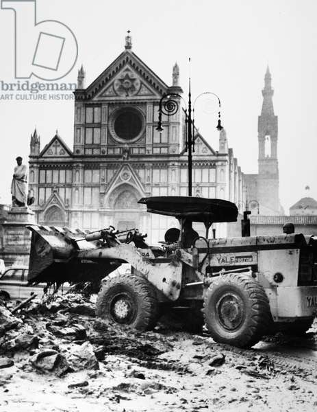 FLORENCE: FLOOD, 1966 A bulldozer clearing mud and debris from a street in front of the Basilica of the Holy Cross in Florence, Italy, after the flood of the Arno River, 8 November 1966.