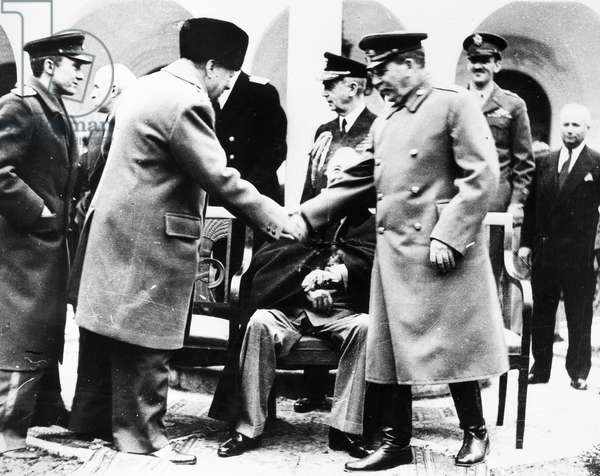 YALTA CONFERENCE, 1945 Prime Minister Winston Churchill of Great Britain shakes hands with Soviet Premier Joseph Stalin at the Livadia Palace at the beginning of the Yalta Conference, February 1945. U.S. President Franklin D. Roosevelt is seated at center.
