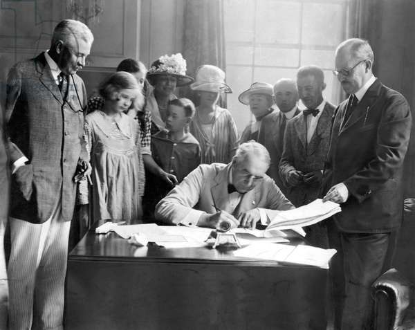 WARREN G. HARDING, 1921 President Harding signing the Congressional Resolution ending the state of war with Austria and Germany at the country home of Senator Frelinghuysen of New Jersey, July 1921.