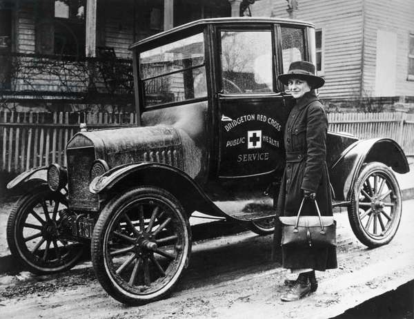 RED CROSS: NURSE & CAR, 1916 A Red Cross nurse with a new Model T Ford, in Bridgeton, Massachusetts. Photograph, 1916.