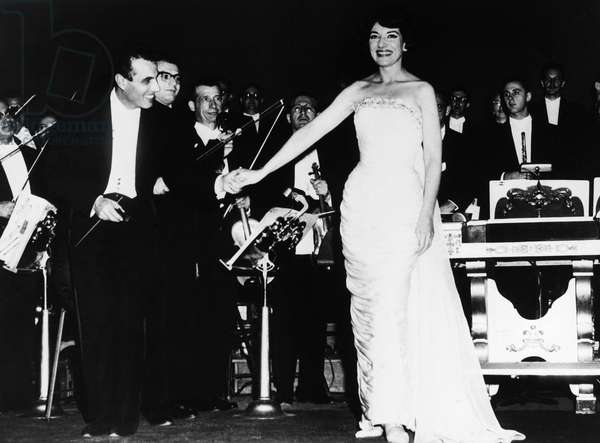 MARIA CALLAS (1923-1977) American operatic soprano. Callas holding hands with conductor Nicola Rescigno during a curtain call after a concert in Kansas City, Missouri, 28 October 1959.