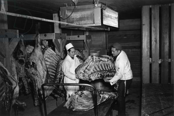 JAPANESE INTERNMENT, 1943 Two men handling a beef carcass at a butcher shop at the Manzanar Relocation Center for Japanese Americans, near Owens Valley, California. Photograph by Ansel Adams, 1943.