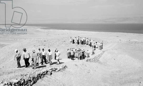 QUMRAN: HOLY LAND Tourist group on their way to the caves at the ancient village of Qumran on the northwestern shore of the Dead Sea, where the Dead Sea Scrolls were excavated in 1947. Photograph by Hanna Safieh, 1958.