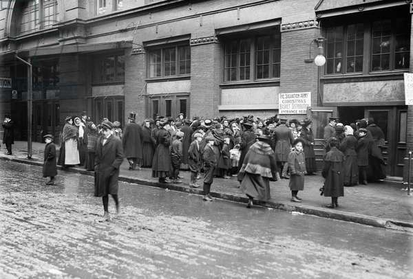 SALVATION ARMY, 1908 Crowd waiting at basket distribution window for Christmas dinner from the Salvation Army, New York City.