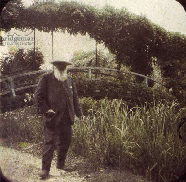 CLAUDE MONET (1840-1926) French impressionist painter, in his garden in Giverny, France. Autochrome, c.1917.