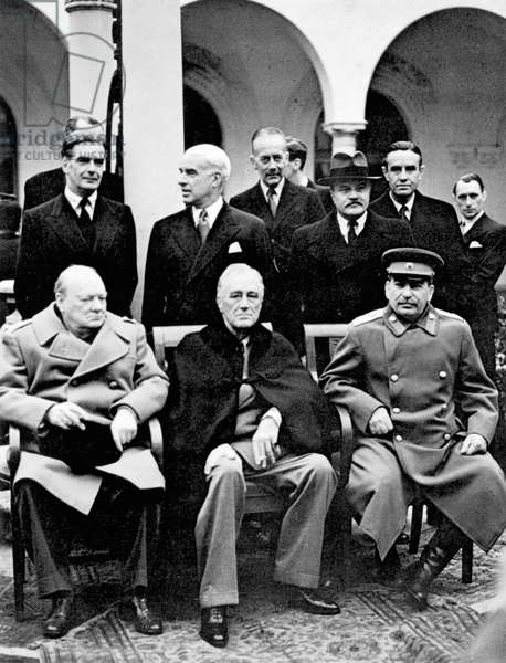 YALTA CONFERENCE, 1945 Winston Churchill, Franklin D. Roosevelt and Joseph Stalin at the Yalta Conference at Livadia Palace, Yalta, Crimea. Standing left to right: Anthony Eden, Edward Stettinius, Alexander Cadogan, Vyacheslav Molotov and W. Averell Harriman. Photograph, February 1945.