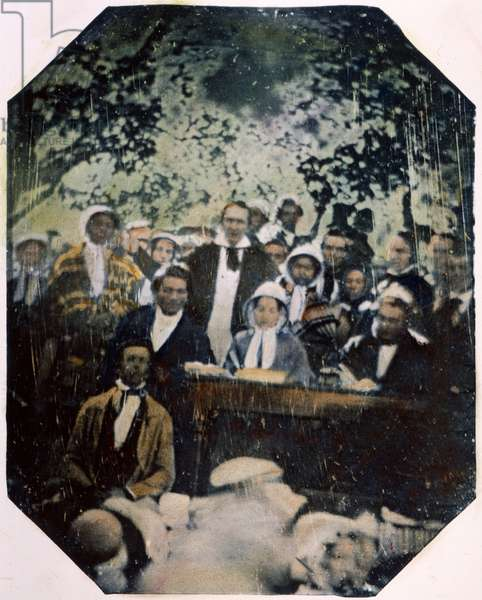 FREDERICK DOUGLASS ( c.1817-1895). American abolitionist. Douglass (seated at table beside a Quaker woman wearing a bonnet) and other abolitionists at the open-air Fugitive Slave Law Convention, Cazenovia, New York, 22 August 1850. Oil over a daguerreotype by Ezra Greenleaf Weld.