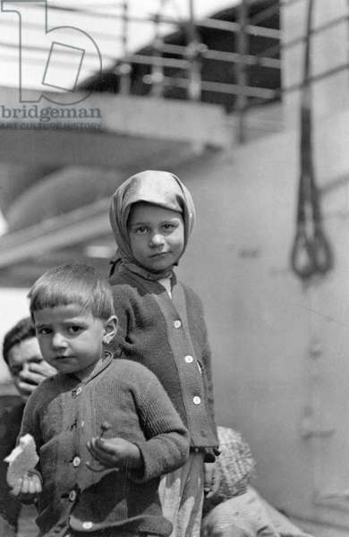 ELLIS ISLAND: IMMIGRANTS Young boy and girl standing before a steamer at Ellis Island, New York, c.1914.