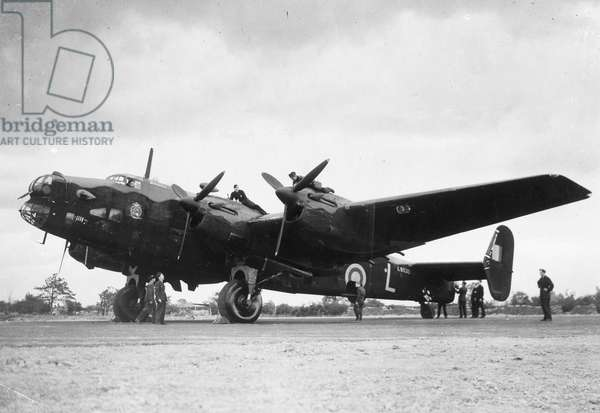 BRITISH BOMBER AIRCRAFT Crew members service a Handley Page Halifax bomber plane of the British Royal Air Force.