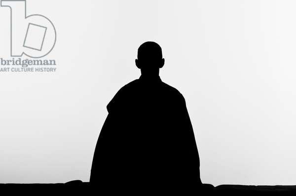 The silhouette of a zen buddhist nun practicing zen-meditation (Zazen) (b/w photo)