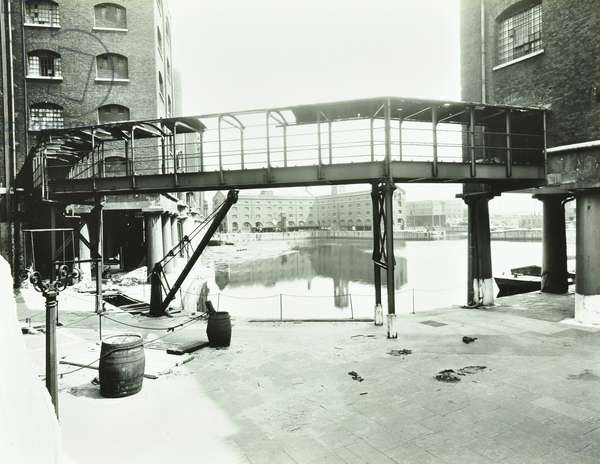 St Katherine Docks, walkway over water, dock buildings, London, 1941 (b/w photo)