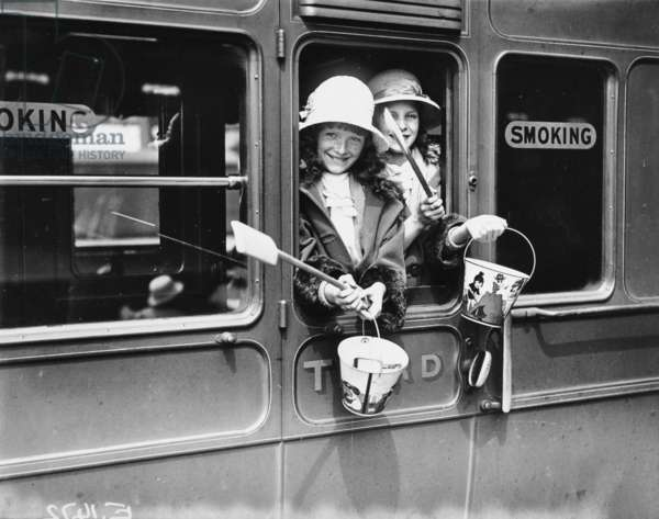 Two young girls (in a third class carriage) leaving London, bound for the seaside. Buckets and spades are brandished out of the train window, 1924 (b/w photo)