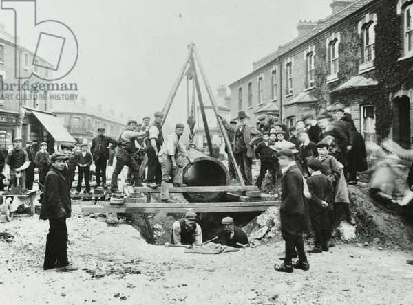 Wandsworth Town Station: removal of a 'Gas Light or Coke Company' gas main, 1906 (b/w photo)