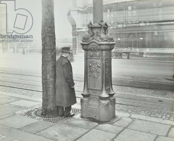 Man stood next to an ornated electric lighting standard, Victoria Embankment, 1932 (b/w photo)