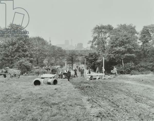 East Hill Estate: construction work in progress, view of workers in a field with machinery, London, 1924 (b/w photo)