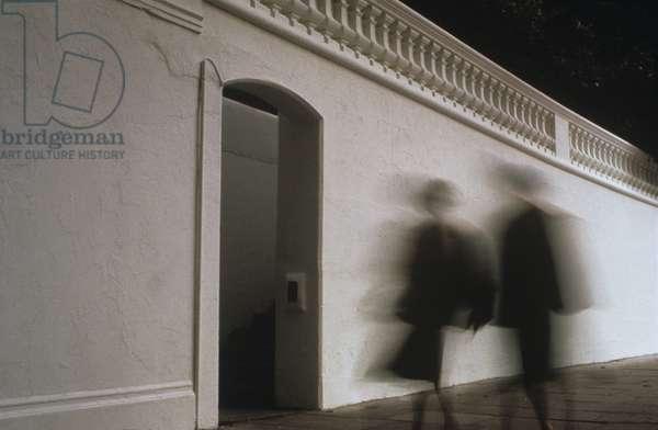 Silhouettes of two women walking along building