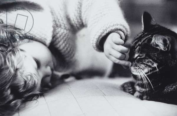 Girl (15-18 months) playing with cat on bed
