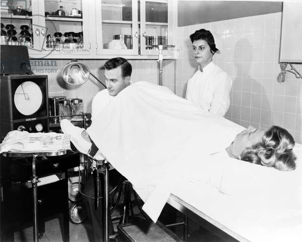 Treatment of infertility: Dr. Hans Marvin of Long Island Jewish Hospital during an examination with tubal insufflation. Photography December 1956.