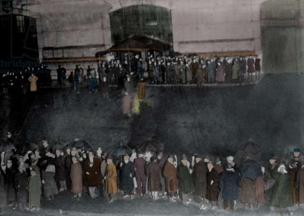 Rain crowd on the Cunard wharf in New York awaits the arrival of the ship Carpathia bringing back the survivors of the Titanic sinking in April 1912. Photography