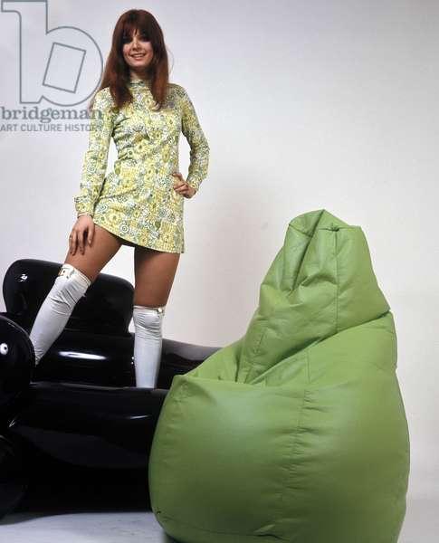 "Design, fashion: the ""Sacco"" pouf is designed by Italian designers Piero Gatti, Cesar Paolini and Franco Teodoro. A young woman poses near the pear-shaped ottoman. 1968."