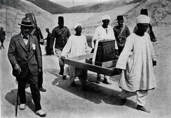 Discovered by Howard Carter and Lord Carnavon from the tomb of Tutankhamun. Thebes (Egypt). Valley of the Kings. 1922.Removal of a chest from the cellar, transported by two Egyptians.