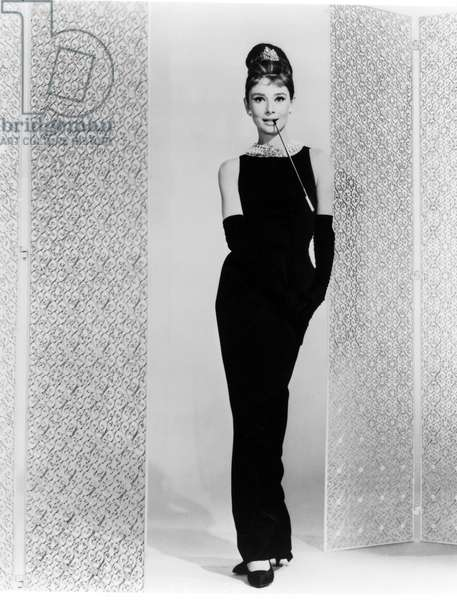 "Comedian Audrey Hepburn in Blake Edwards' """" Diamonds sur canape"" (Breakfast at Tiffany's), she wears a sheath dress and a cigarette smoker in her mouth. The costumes for the film are by Hubert de Givenchy. 1961"