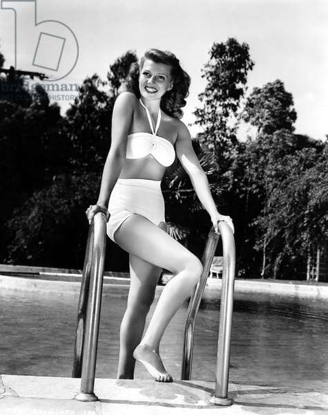 American comedian Rita Hayworth (1918-1987) posing in a swimsuit (pin up) by a pool 1945