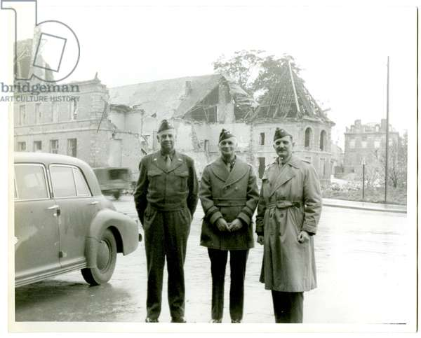 Shown standing outside a bombed out building (b/w photo)