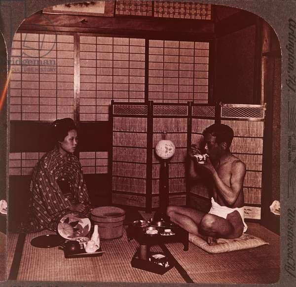Man eating an evening meal at an inn, near Hiroshima, Japan, c.1904 (b/w photo)
