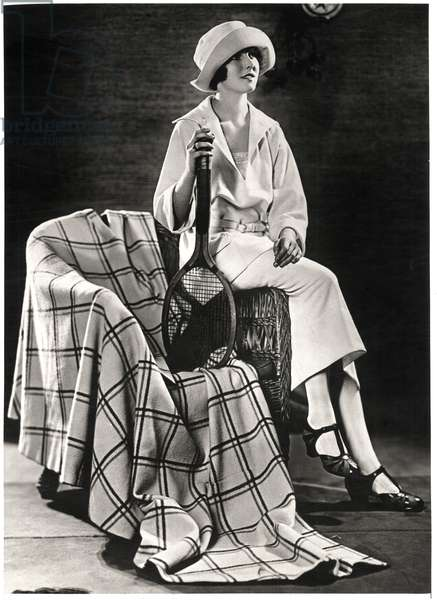 Fashionable Young Woman in White Jersey Sport Costume with Plaid Coat-Cape, Holding Tennis Racquet, Portrait, c.1922