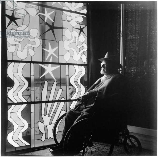 Henri Matisse (1869-1954) in Wheelchair Looking at the work 'Nuit de Noel' (Christmas Eve), at his home in the Régina, Nice, France, 1952 (b/w photo)