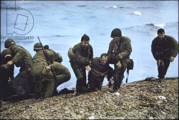 U.S. Soldiers of 116th Regiment of the 29th Infantry Division being helped to shore after Arriving at Omaha Beach in Life Raft after their Landing Craft Vehicle, Personnel (LCVP) had been Sunk off Beachhead, Nicholas Russin (3rd from right), being dragged onto shore by two Soldiers, Operation Overlord, Battle of Normandy, France, June 7, 1944 (photo)