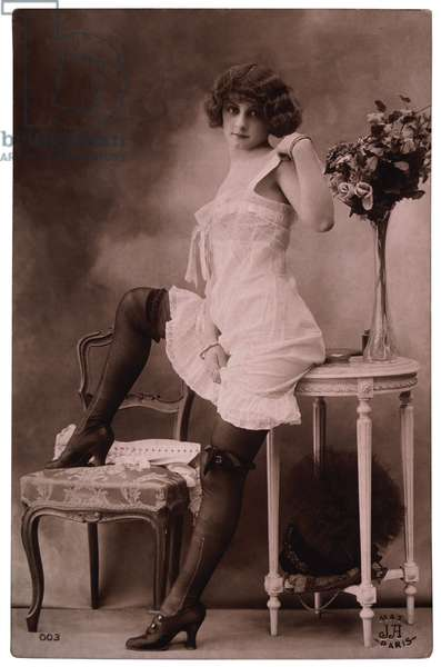 French Lingerie Model Leaning on Table With One Leg Raised on Chair, 1920