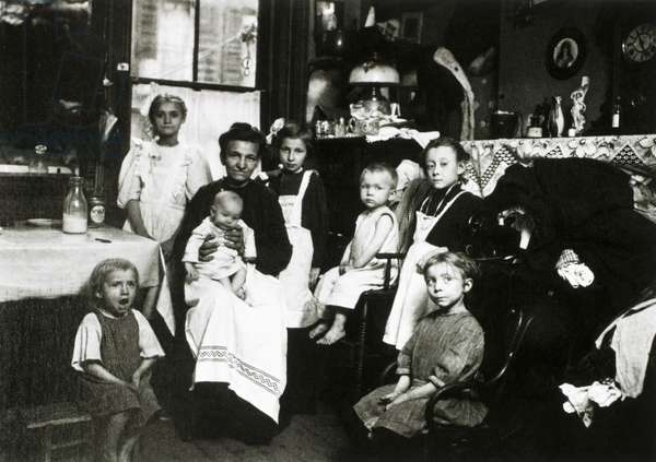 Mother and children in a tenement apartment, New York City, USA, 1910 (b/w photo)