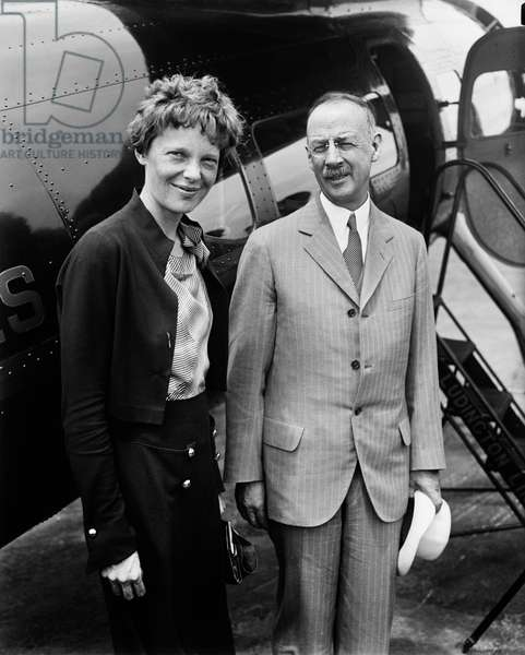 Amelia Earhart (L), Portrait with Man in front of Airplane, Harris & Ewing, 1932 (b/w photo)