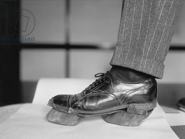 Policeman Trying on Cow Shoe used by Moonshiners during Prohibition, Washington DC, USA, 1924 (b/w photo)