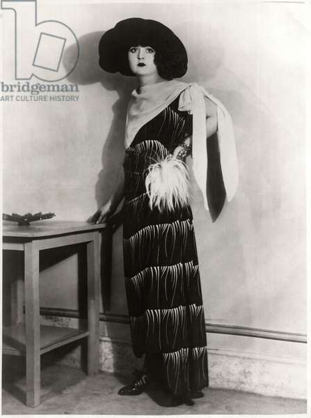 Fashionable Young Woman in Long Dress with Feather Pompom at Waist and Crepe Kerchief Tied Over Shoulder, with Hat, Portrait, c.1922