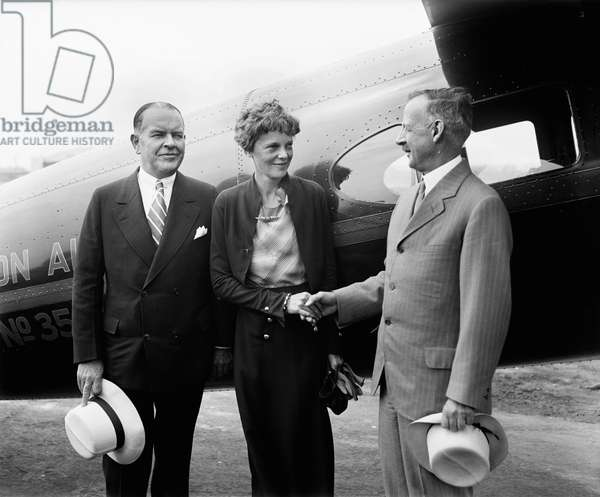 Amelia Earhart, Center, Portrait Shaking Hands with Man in front of Airplane, Harris & Ewing, 1932 (b/w photo)