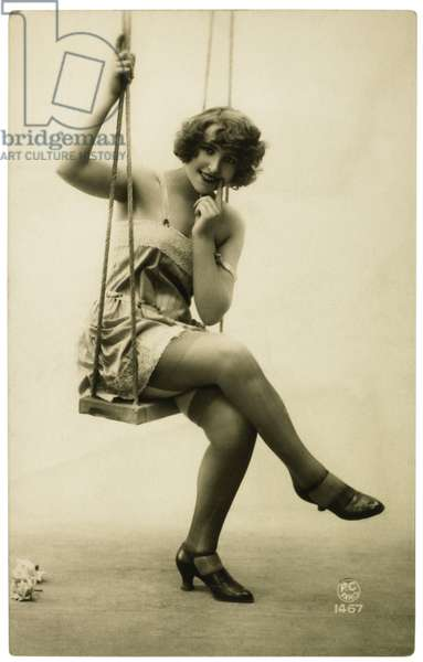 Lingerie model seated on a swing, c.1920 (b/w photo)